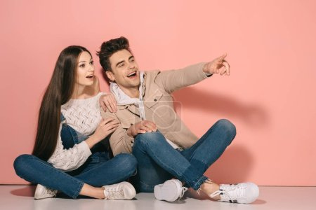 Photo for Brunette and beautiful girlfriend in denim overalls and handsome boyfriend sitting on floor and pointing with finger - Royalty Free Image