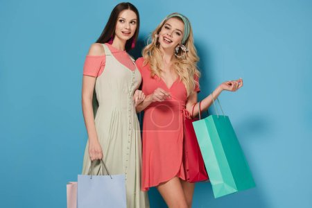 Photo for Smiling brunette and blonde women in dresses holding shopping bags and looking at camera - Royalty Free Image