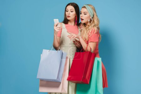 Photo for Surprised brunette and blonde women in dresses holding shopping bags and using smartphone - Royalty Free Image