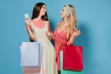 Photo pour Sourire de femme brune tenant smartphone et femme blonde en robe tenant des sacs à provisions - image libre de droit