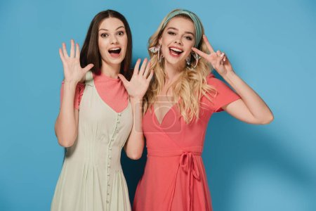 Photo for Smiling brunette and blonde women in elegant dresses showing gestures - Royalty Free Image