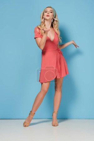 Photo pour Femme séduisante et blonde en robe élégante soufflant air baiser sur fond bleu - image libre de droit