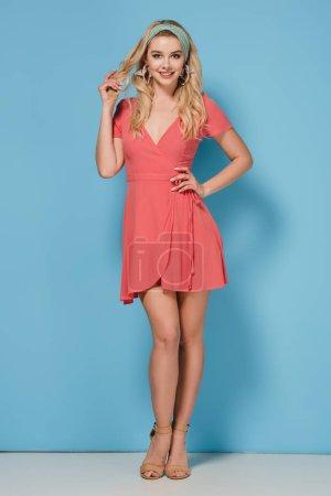 Foto de Mujer atractiva y rubia en vestido elegante con mano en cadera sonriendo y mirando a cámara - Imagen libre de derechos