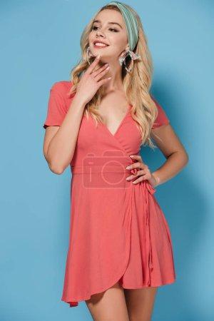 Photo pour Femme séduisante et blonde dans une robe élégante avec la main sur la hanche souriant et en regardant loin - image libre de droit