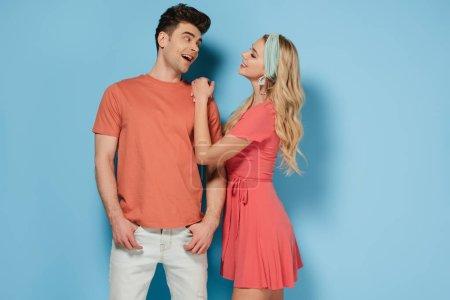 Photo pour Femme blonde en robe élégante et bel homme parler et regarder les uns les autres - image libre de droit