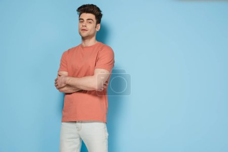 Photo for Handsome and brunette man in t-shirt with crossed arms looking at camera - Royalty Free Image