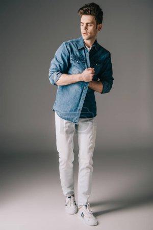 Foto de Hombre guapo triste camisa denim y jeans mirando lejos en fondo gris - Imagen libre de derechos