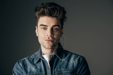 Photo for Handsome and brunette man looking at camera isolated on black - Royalty Free Image