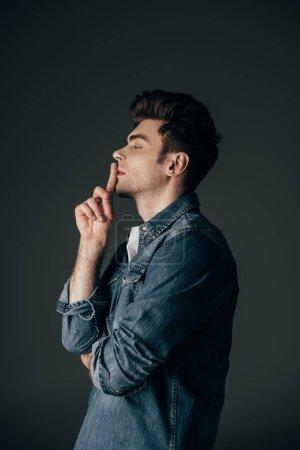 Photo pour Vue latérale d'un homme beau et brune en chemise en denim montrant shh geste isolé sur fond noir - image libre de droit