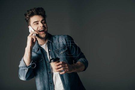Foto de Sonriente y morena hombre en camisa de mezclilla sosteniendo taza de papel y hablando en teléfono inteligente aislado en negro - Imagen libre de derechos