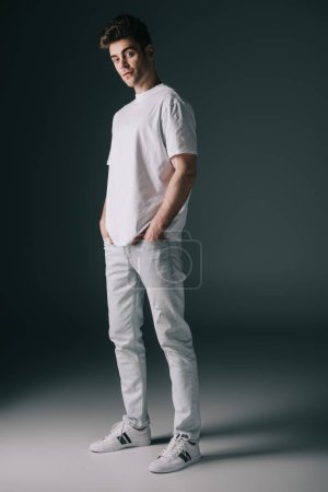 Photo for Handsome man in white t-shirt and jeans with hands in pockets looking at camera - Royalty Free Image