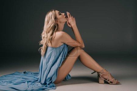 Photo pour Vue latérale d'une femme belle et blonde en robe élégante sur fond gris - image libre de droit