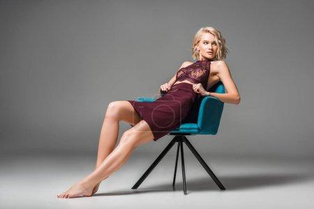 Photo pour Belle jeune femme élégante dans les vêtements de Bourgogne s'asseyant dans le fauteuil et posant sur le gris avec l'espace de copie - image libre de droit
