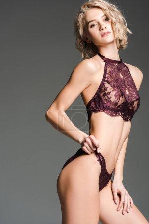 Photo pour Belle fille sexy en lingerie Bourgogne regardant l'appareil-photo et posant isolé sur le gris - image libre de droit