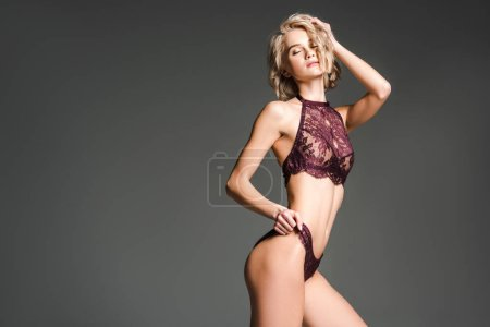 Photo for Beautiful sexy girl in burgundy lingerie posing isolated on grey with copy space - Royalty Free Image