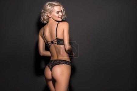 Photo pour Vue de dos de belle fille sexy en lingerie de dentelle posant sur le noir avec l'espace de copie - image libre de droit