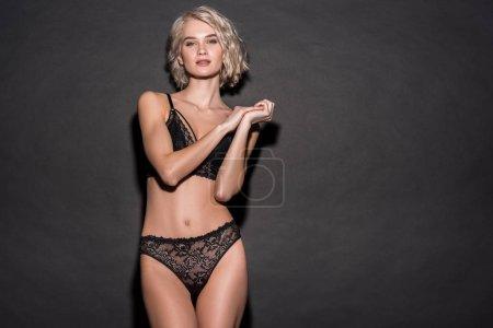 Photo pour Belle fille sexy en lingerie de dentelle regardant l'appareil-photo et posant sur le noir avec l'espace de copie - image libre de droit