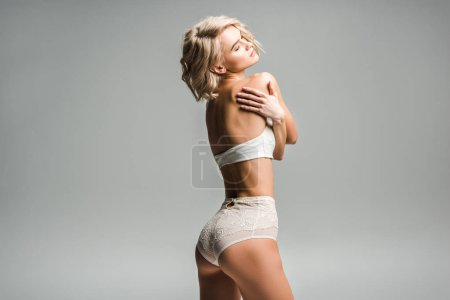 Photo for Beautiful seductive girl in lingerie posing isolated on grey with copy space - Royalty Free Image