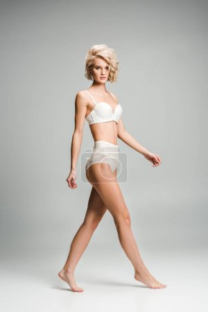 Photo for Beautiful seductive blonde young woman in lingerie posing and looking at camera on grey - Royalty Free Image