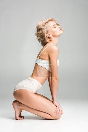 Photo pour Belle fille blonde sexy en lingerie s'asseyant et posant sur le gris - image libre de droit