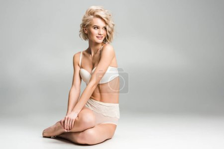 Photo for Beautiful sexy young woman in lingerie sitting, smiling and posing on grey with copy space - Royalty Free Image