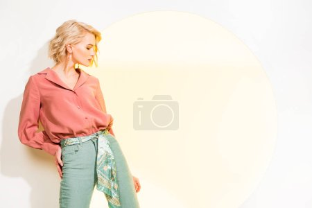 Photo for Beautiful stylish girl in colorful clothes posing on white with yellow circle and copy space - Royalty Free Image
