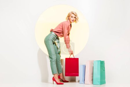 Photo for Beautiful stylish girl holding shopping bag and looking at camera on white with yellow circle - Royalty Free Image