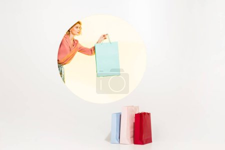 Photo pour Beau jeune femme élégant retenant le sac de magasinage sur le blanc avec le cercle jaune et l'espace de copie - image libre de droit