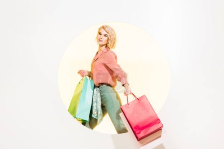 Photo for Beautiful stylish girl looking at camera and holding shopping bags on white with yellow circle - Royalty Free Image