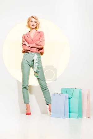 beautiful stylish girl with arms crossed posing near shopping bags on white with yellow circle