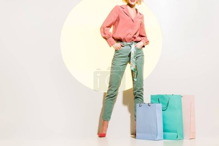 Photo for Cropped view of stylish girl posing near shopping bags on white with yellow circle - Royalty Free Image