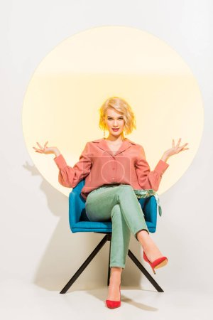 Photo for Beautiful stylish girl in colorful clothes sitting in armchair and gesturing with hands on white with yellow circle - Royalty Free Image