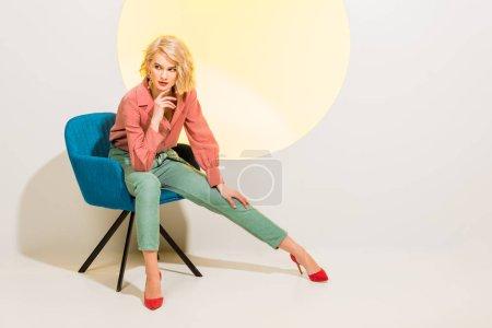 Photo pour Belle fille élégante dans des vêtements colorés s'asseyant dans le fauteuil sur le blanc avec le cercle jaune et l'espace de copie - image libre de droit
