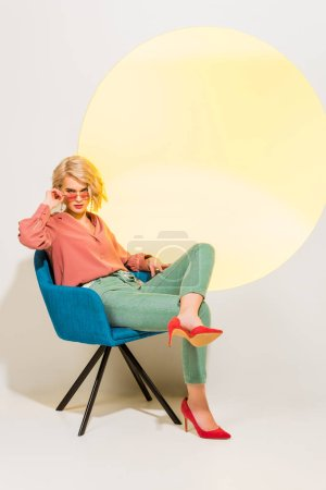 Photo for Beautiful stylish young woman in colorful clothes sitting in armchair on white with yellow circle - Royalty Free Image