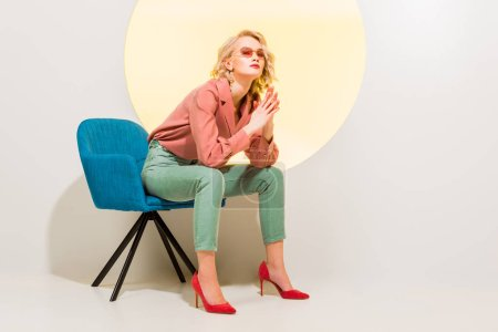 Photo for Beautiful stylish girl in colorful clothes and sunglasses sitting in armchair on white with yellow circle - Royalty Free Image