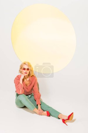 Photo for Beautiful stylish girl in colorful clothes and sunglasses posing on white with yellow circle - Royalty Free Image