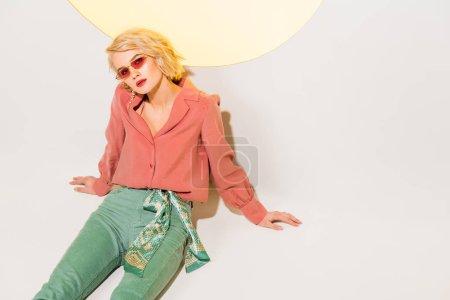 Foto de Hermosa mujer joven con estilo en las gafas de sol sentado y posando en blanco con círculo amarillo - Imagen libre de derechos