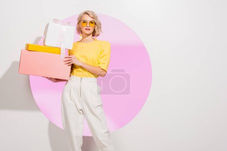 Photo for Beautiful stylish girl holding gift boxes on white with pink circle and copy space - Royalty Free Image