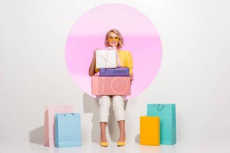 Foto de Hermosa chica de moda posando con coloridas cajas de regalo y bolsas de compras en blanco con círculo rosado - Imagen libre de derechos
