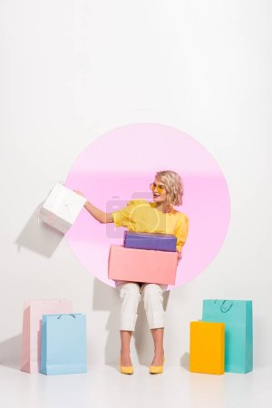 Photo for Beautiful fashionable girl posing with colorful gift boxes and shopping bags on white with pink circle - Royalty Free Image