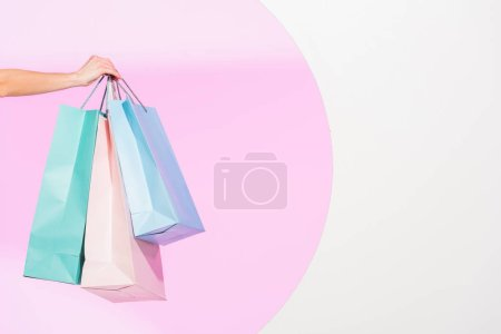 Photo for Cropped view of young woman holding colorful shopping bags on white with pink circle - Royalty Free Image