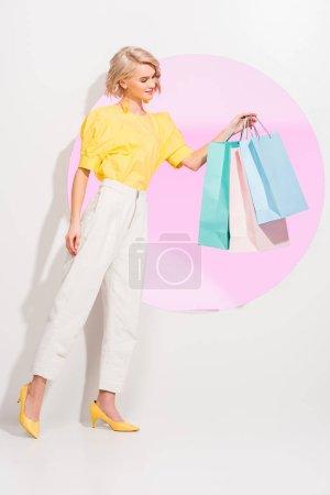 Photo pour Beau jeune femme élégant retenant des sacs de magasinage colorés sur le blanc avec le cercle rose - image libre de droit