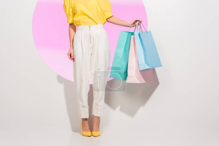 Photo for Partial view of stylish girl holding colorful shopping bags on white with pink circle - Royalty Free Image