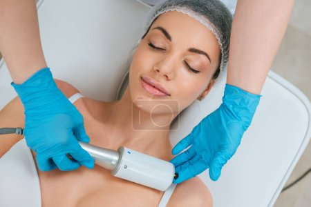 Photo for Partial view of cosmetologist in rubber gloves doing endospheres therapy for chest - Royalty Free Image