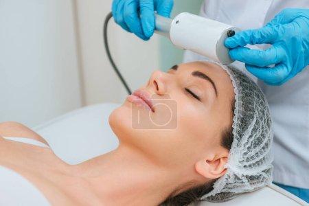 Vista parcial del cosmetólogo haciendo terapia endoscópica para la cara