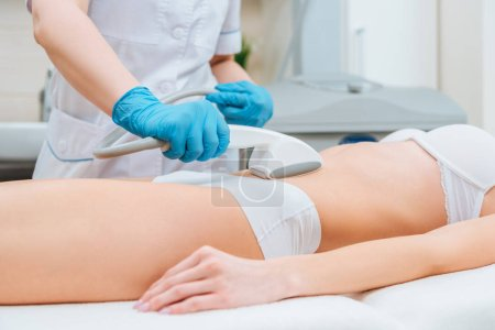 Photo for Cropped view of cosmetologist with roller doing belly starvac massage - Royalty Free Image
