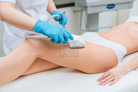 Photo for Cropped view of cosmetologist with roller doing leg starvac massage - Royalty Free Image