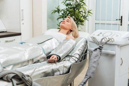 Photo pour Jeune fille blonde, couché avec les yeux fermés au cours de la séance de pressothérapie en clinique - image libre de droit