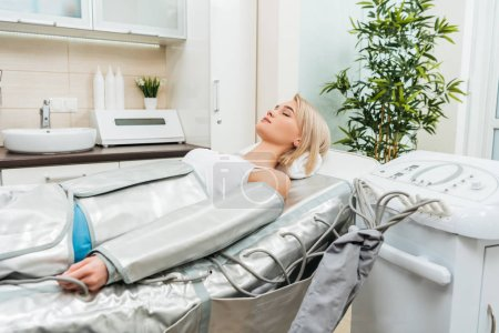 Photo for Blonde girl lying with closed eyes during pressotherapy session in clinic - Royalty Free Image