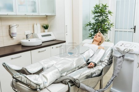 Photo for Blonde girl lying on beauty couch during pressotherapy session in clinic - Royalty Free Image